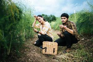 Young farmer couple harvests fresh asparagus in field