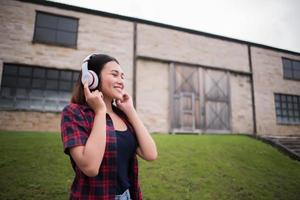 Close-up of young hipster woman listening to music outdoors