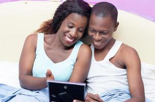 Couple looking at a photo in bed