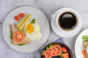 Boiled eggs, carrots and tomatoes with spoon and coffee cup photo