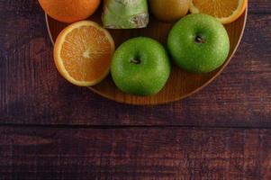Orange slices with apple, kiwi and broccoli on a wooden plate