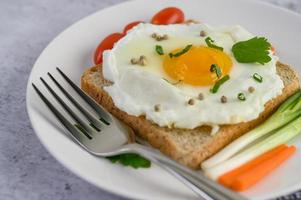 un huevo frito sobre una tostada cubierta con semillas de pimiento con zanahorias y cebolletas foto