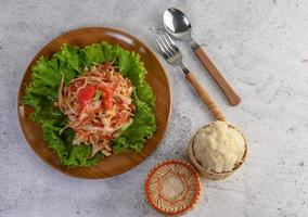 Thai papaya salad with sticky rice, spoon and fork