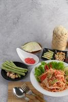 Thai salad with sticky rice, dried shrimp, spoon and fork photo