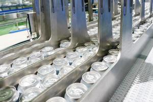 Conveyor line carrying thousands aluminum beverage cans at factory. Concept of industrial growth