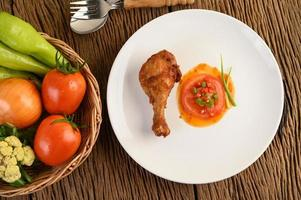 Fried chicken legs with sauce and veggies photo