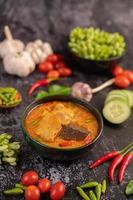 Chicken curry in a black cup with garlic and peppers photo