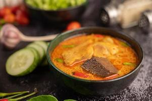 Chicken curry in a black cup with garlic and peppers