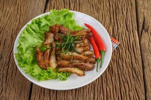 Grilled pork neck on a wooden table photo