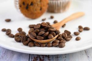 Granos de café en una cuchara de madera y cupcakes de plátano en una mesa de madera blanca foto
