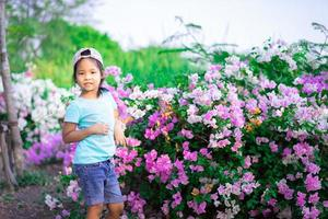 Little Asian girl wearing a cap with bougainvillea flower in the park