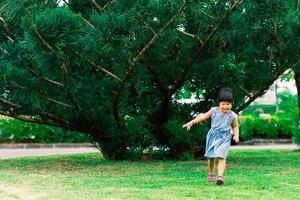 A happy little girl in a dress running in the park