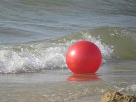 Red ball floating on waves next to a sandy beach photo