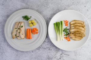 Pechuga de pollo al vapor sobre un plato blanco con cebolletas y zanahorias