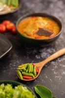 Chicken curry in a black cup with little peppers