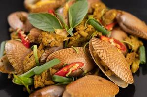 Clams fried with curry powder on a black plate photo