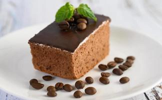 Chocolate cake with coffee beans on a wooden surface