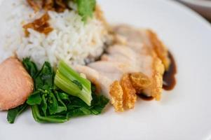 Crispy pork on a white rice topped with sauce