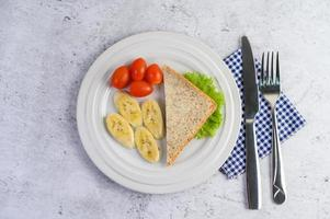 Bread with banana and tomatoes on a white plate