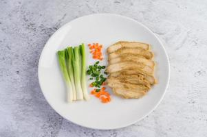 Steamed chicken breast on a white plate with spring onions and carrots