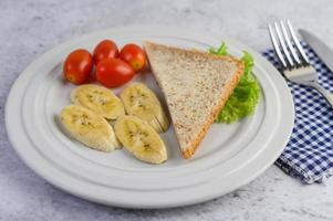 Pan con plátano y tomates en una placa blanca. foto