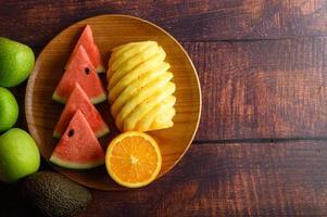 sandía, naranja y piña cortadas en trozos en una placa de madera