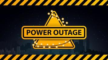 Power outage, yellow warning logo wrapped with a garland on the background of the city without electricity