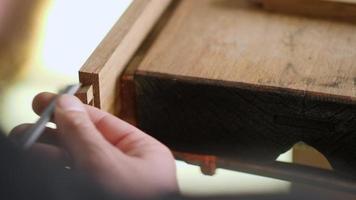 menuisier sculpte un joint en queue d'aronde avec un ciseau à bois