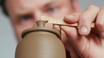 Potter Removing Excess Clay from A Clay Teapot