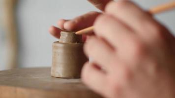 oleiro decora uma peça de cerâmica video