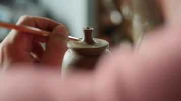 Potter Decorates The Lid of A Clay Teapot