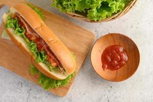 Hotdog with lettuce and tomato on a wood cutting board