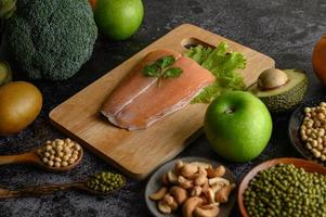 Legumes, fruit and salmon fish on a wooden chopping board