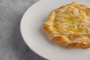 Bocadillo de pan de torsión de almendras en una placa blanca.