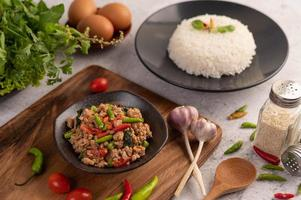 Ensalada picante de cerdo picada con arroz, chili y tomates en una placa negra