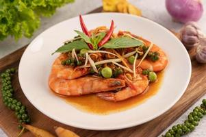 Chu-chi shrimp on a plate with fresh pepper seeds