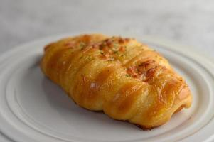 A sausage bread roll with hotdog on white plate photo