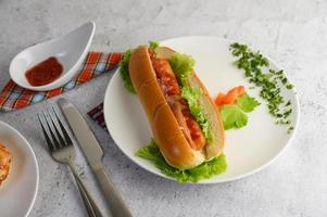 A hotdog placed in white dish beautifully photo