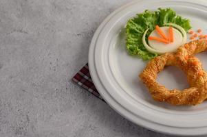 pretzel en un plato blanco con lechuga y zanahorias foto