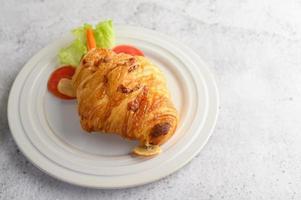 Un croissant con hotdog en plato blanco