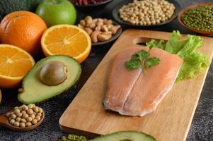 Legumbres, frutas y pescado salmón sobre una tabla de cortar de madera foto