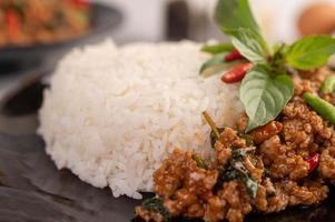 Ensalada picante de cerdo picada con arroz, chile y tomates en un plato negro