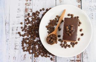 Pastel de chocolate en un plato blanco y granos de café. foto