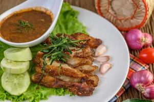 Pork neck grilled on a white plate with red onion, tomato and chili on a wooden table photo