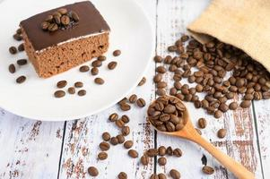 Chocolate cake on a white plate and coffee beans