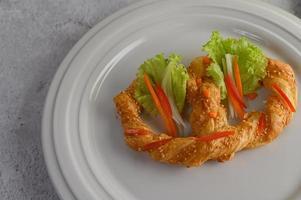 Pretzel suave recién horneado en un plato blanco foto