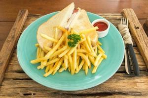 Ham and cheese sandwich with french fries on blue plate