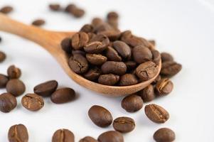 Granos de café en una cuchara de madera sobre una mesa de madera blanca foto