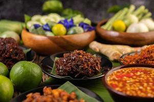 Chili paste served on banana leaves surrounded by long beans, lime, chili and eggplant