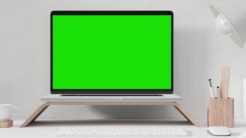 portátil sobre soporte de madera con pantalla verde video